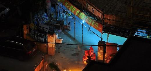 Pogrzeb w środkui nocy na osiedlu w dzielnicy Pudong. Członek rodziny zmarłej osoby spala tekturowy dom. Wcześniej spalono pieniądze i inne przedmioty używane każdego dnia